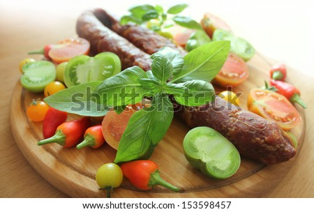 Sausage, peppers, basil  and tomato on a wooden cutting board