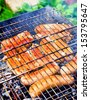 Sausages are fried on coals. - stock photo