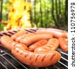 Sausages on a grill. In the background a bonfire in the forest. - stock photo