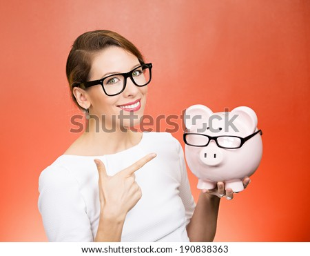 Save money. Closeup portrait happy business woman in glasses, employee, optician, holding piggy bank, pointing with finger isolated red background. Financial concept. Positive face expression, emotion