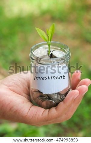 save money for investment concept plant growing out of coins