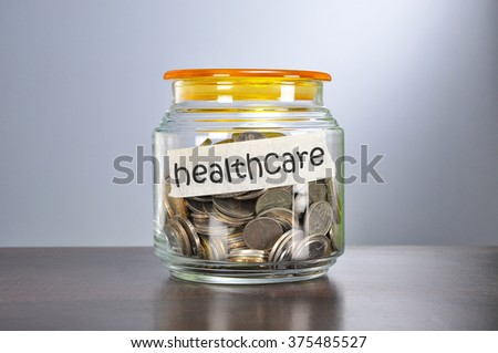Saving concept of coins in the glass jar for health care  purpose.