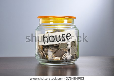 Saving concept of coins in the glass jar for house  purpose.