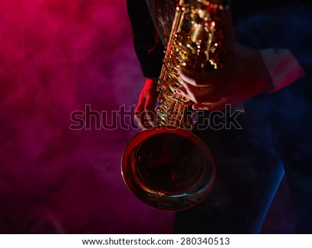Saxophonist, beautiful young woman, smoky stage on background