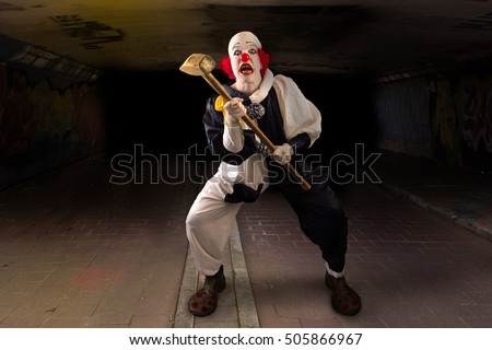 scary clown with a hammer standing in a tunnel