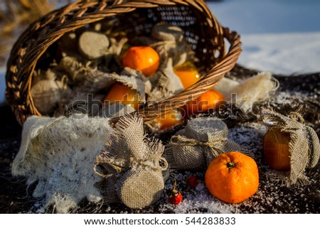 Scattered from wicker basket jars with tangerine jam and tangerine on the snow