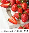 Scattering of fresh red strawberries on an old white cutting board. - stock photo