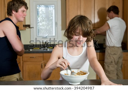 Scene of family at breakfast, with focus on younger brother, age twelve - candid shots
