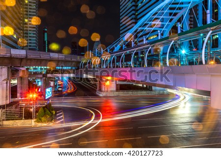 Scene of the light trails from the vehicles at the intersection with a walk-over pedestrain bridge and light bokeh in the foreground