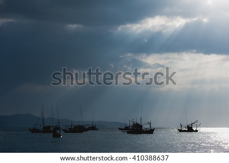 Scenery of fishing boats and yachts with sunlight shining through cloudy sky and reflections of golden clouds on smooth water, in Thailand