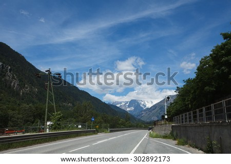 Scenic highway Milano - Aosta with the view of snow covered mountains on a sunny day in summer, Italy