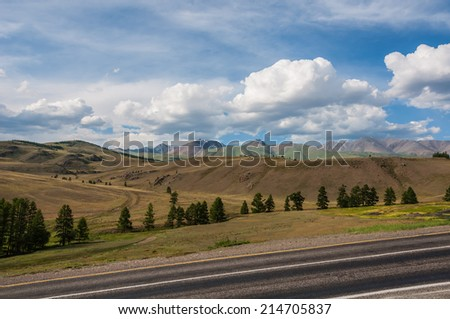 Scenic road through the valley in the mountains on a sunny summer day