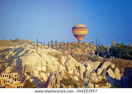 Scenic vibrant view of balloons flight in Cappadocia valley in sunrise rays.