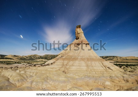 Scenic view of a desertic landscape at night with star trails in Bardenas reales, Navarra, Spain.