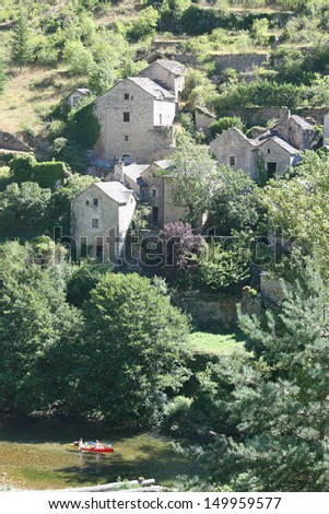 Scenic view of an old french village with river in foreground, Gorges du Tarn, Lozere, France.