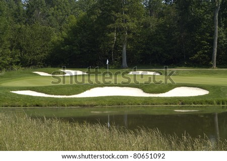 scenic view of golf course and water with lush trees in background.