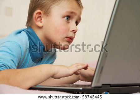 School-age boy sitting in front of the monitor laptop at home on the couch.
