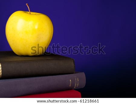 School Books stacked with an apple on top, a blue background and space on the right for your text.