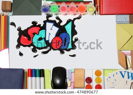 school text word painted graffiti with smiley eyes on paper near pencils markers computer mouse chalk ruler paint palette wooden cube notebook and alphabet on white background