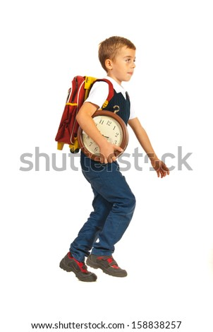Schoolboy in late running to school and holding big clock isolated on white background
