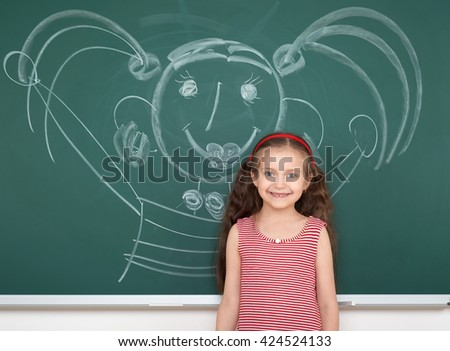 schoolgirl child in red striped dress drawing happy man on green chalkboard background, summer school vacation concept