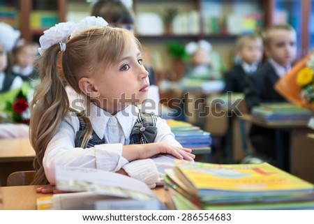Schoolgirl with folded hands sitting at school desk at lesson, copyspace