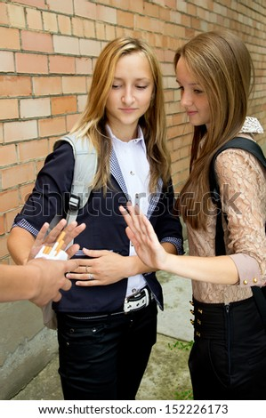 Schoolgirls indicate stop smoking in the street
