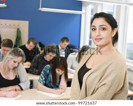 Schoolteacher in front of pupils in the classroom