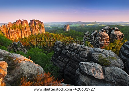 Schrammsteine, beautiful evening view over sandstone cliff into deep misty valley in Saxony Switzerland, evening background, the fog is orange due to sunset, star sun on sky, Germany. Last rock light.