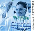 Science graphic against female scientist analyzing young plants at lab - stock photo