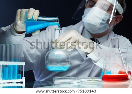 Scientist pouring fluid substances from one beaker into another