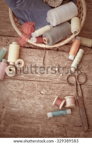 Scissors, bobbins with thread and needles, striped fabric. Old sewing tools on the old wooden background. Vintage Background.