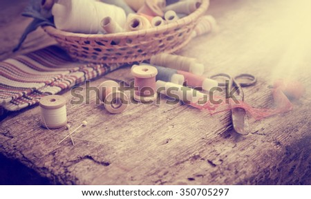 Scissors, bobbins with thread and needles, striped fabric. Old sewing tools on the old wooden background. Vintage Background