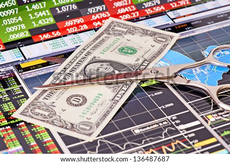 Scissors cutting  one-dollar  banknote.Financial charts and columns of prices as background. Selective focus