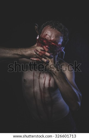 Screaming, naked man with blindfold soaked in blood