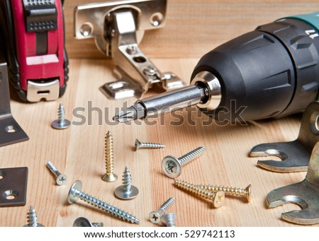 Screwdriver with screws on wooden background