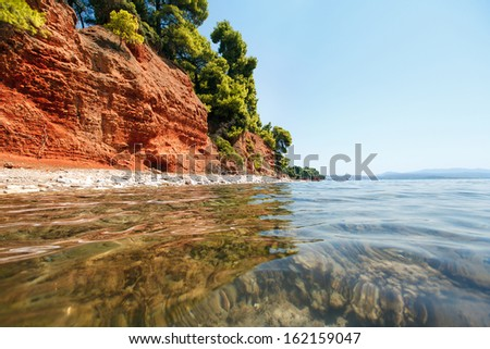 Sea beach with red ground and pine trees in Greece, Halkidiki