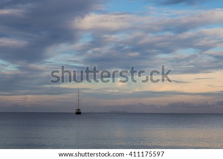 Seascape - boat without sails on the ocean surface  against the morning cloudy sky. Outlines of  islands on the horizon. Fiji.