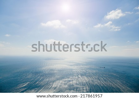 Seascape. Cargo ship in the sea on the background of the sky with white clouds. Storm at sea with divorces from the wind and the shadows of the clouds. Photographed in the summer on a hot sunny day.