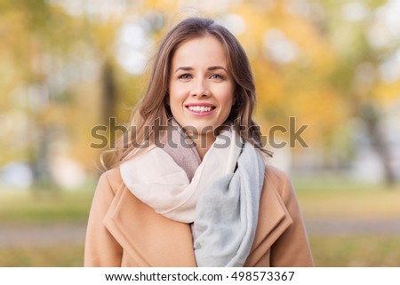 season, emotions, facial expression and people concept - beautiful happy young woman smiling in autumn park