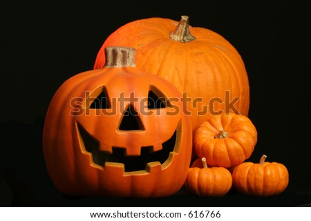 seasonal harvest of squash and a Halloween face carved in a jack o lantern