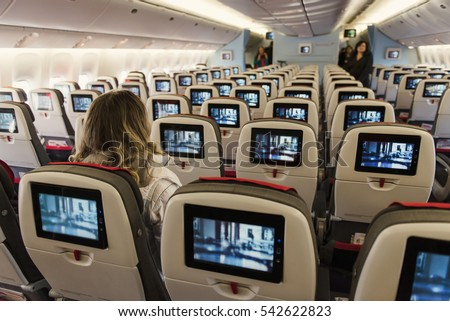 Seats on board of airplane. Cabin of economy class with tv screens and first passengers.