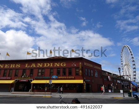 SEATTLE-- JUNE 24: Miners Landing at Pier 57 with signs of tourist businesses and of Great Ferris Wheel on June 24, 2016 in Seattle, WA. Seattle's waterfront is a very popular tourist destination.