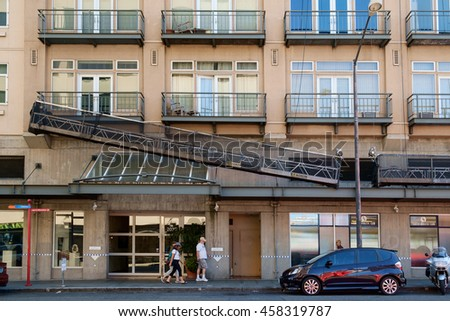 Seattle, USA July 24, 2016: Group of people walk below window washing platform that is hanging at an angle from side of building