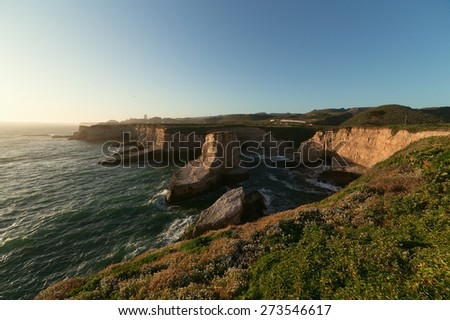 Secluded ocean beach with huge scaur on pacific coast of California in soft sunset light