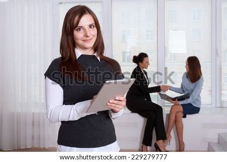Secretary smiling woman reads information from the tablet in the foreground, and her colleagues have a talking in the background