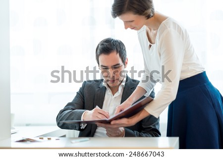 Secretary standing in the office presenting a document in a file to her boss seated at his desk for his clearance and signature.