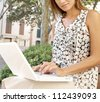 Section of a businesswoman using a pc laptop computer while sitting on a wooden bench in a city park. - stock photo