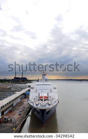Seen from the from high up an ocean going cruise liner berthed up at a dock with morning sky clouds