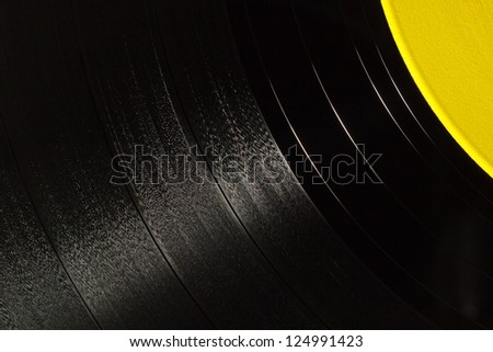 Segment of vinyl record with yellow label showing the texture of the grooves